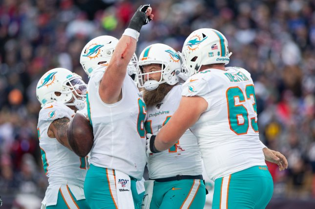 Miami Dolphins quarterback Ryan Fitzpatrick (C) is congratulated by teammates after scoring a touchdown in the third quarter against the New England Patriots on Sunday at Gillette Stadium in Foxborough, Mass. The Dolphins defeated the Patriots 27-24. Photo by Matthew Healey/UPI