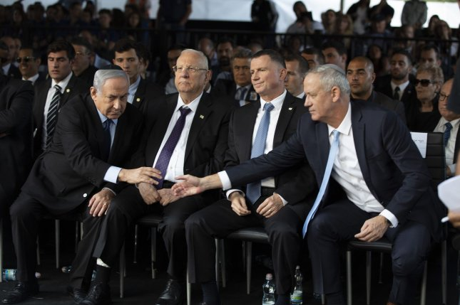Blue and White party chief Benny Gantz (R) reaches out to shake hands with Israeli Prime Minister Benjamin Netanyahu during a state memorial ceremony for Yitzhak and Leah Rabin, in Jerusalem, Israel, on November 10, 2019. File Photo by Heidi Levine/UPI