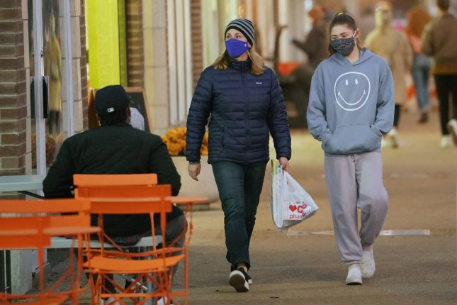 Masked pedestrians walk past empty tables in University City, Mo., on Tuesday. Due to a surge in COVID-19 cases, St. Louis County Executive Dr. Sam Page has ordered all restaurants in St. Louis County to close indoor seating. Photo by Bill Greenblatt/UPI