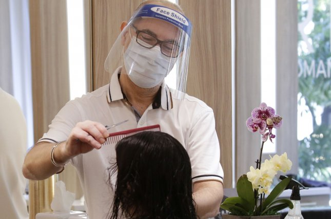 A stylist wears a protective face mask while giving a haircut to a client at Roman K. Salon Luxury Hair Salon when New York City. File photo by John Angelillo/UPI