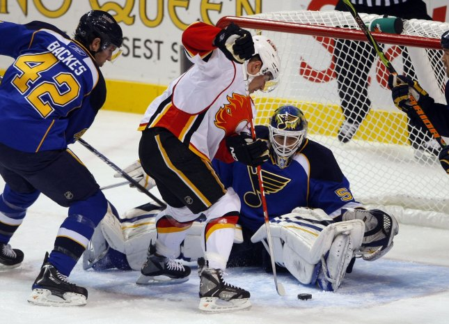 Calgary Flames Michael Cammalleri (13) tries to push the puck by St. Louis Blues goaltender Chris Mason while Blues David Backes (42) tries to clear the zone in the first period at the Scottrade Center in St. Louis on December 16, 2008. Calgary defeated St. Louis 6-3. (UPI Photo/Bill Greenblatt)