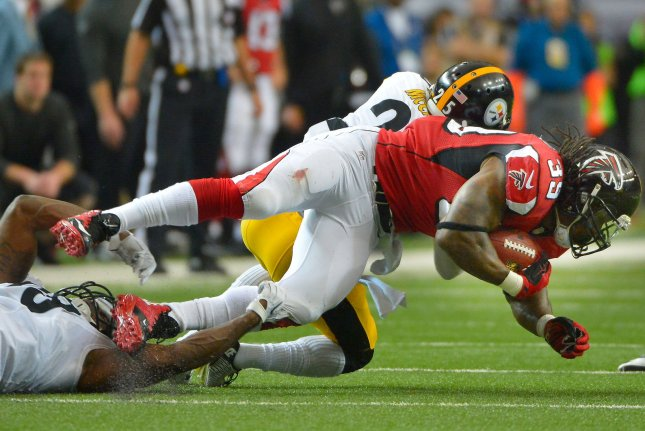 Atlanta Falcons running back Steven Jackson (39) is tripped up by Pittsburgh Steelers' Vince Williams (L) and Brice McCain (C) during the first half of their NFL game at the Georgia Dome on December 14, 2014, in Atlanta. UPI/David Tulis