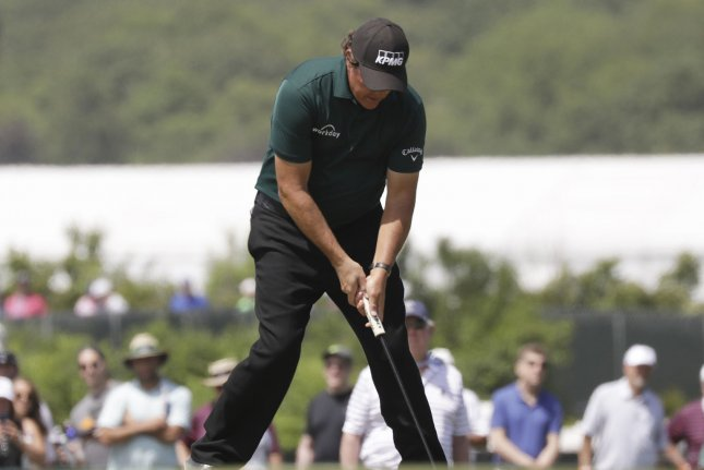 Phil Mickelson hits a putt on a ball that was still rolling on the 13th green in the third round at the 118th U.S. Open Championship on Saturday at Shinnecock Hills Golf Club in Southampton, N.Y. Photo by John Angelillo/UPI
