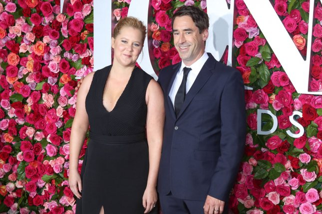 Amy Schumer (L) and her husband Chris Fischer. Schumer discussed Fischer's autism diagnosis on Late Night with Seth Meyers. File Photo by Serena Xu-Ning/UPI