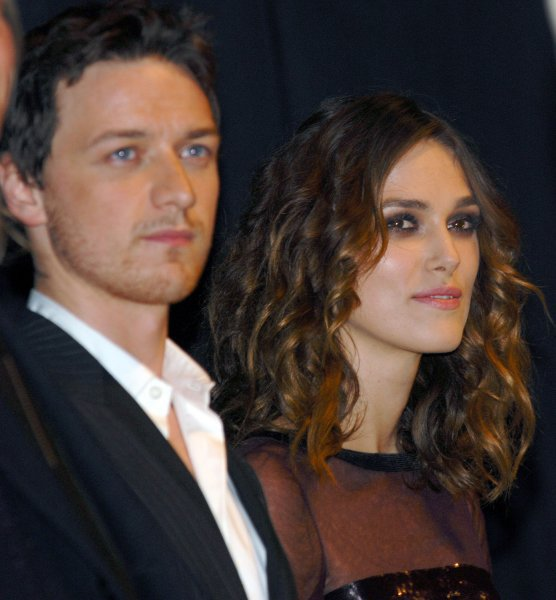 Keira Knightley (R) and James McAvoy listen as director Joe Wright introduces the cast onstage at the Toronto International Film Festival premiere of Atonement at the Elgin Theater in Toronto, Canada on September 10, 2007. (UPI Photo/Christine Chew)