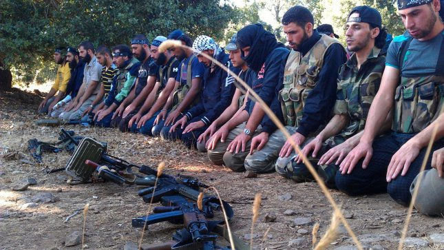 Members of the Free Syrian Army perform prayers in Damascus on August 13, 2012. UPI