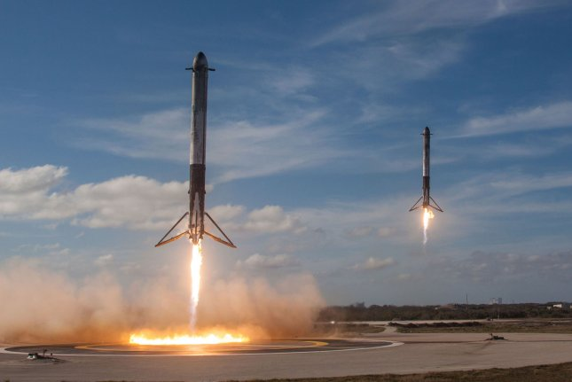 Two of the booster rockets return to to be reused after SpaceX launched its next-generation Falcon Heavy rocket from Kennedy Space Center last year. File Photo by SpaceX/UPI