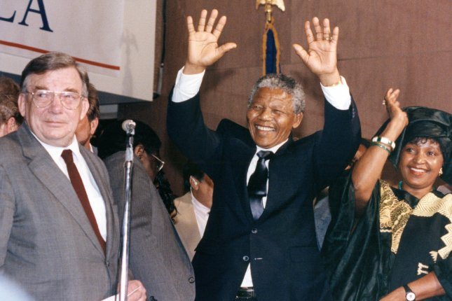 South African leader Nelson Mandela (C) and wife Winnie (R) wave to the crowd of supporters June 25, 1990. On February 11, 1990, Mandela was released after 27 years in prison. File Photo by Martin Jeong/UPI