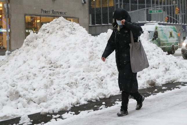 A masked pedestrians walks past piles of snow on Sixth Avenue in New York City on Thursday. Photo by John Angelillo/UPI