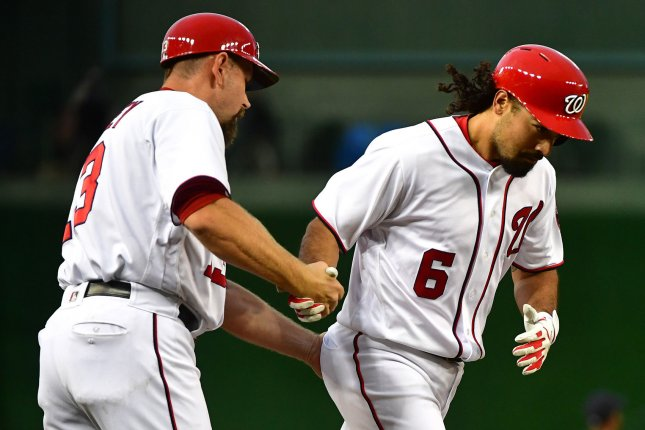 Washington Nationals third baseman Anthony Rendon (6) celebrates with third base coach Bob Henley after hitting a home run. File photo by Kevin Dietsch/UPI