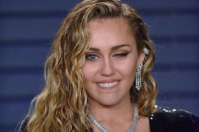 Miley Cyrus winks at photographers on the carpet as she arrives for the Vanity Fair Oscar Party in Beverly Hills, Calif., on Sunday. Photo by Christine Chew/UPI