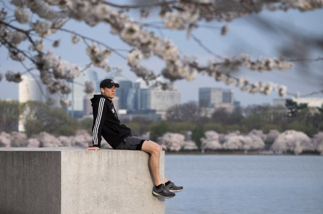 A man sits and overlooks the Tidal Basin as cherry blossoms bloom in Washington, D.C., on Friday. The National Park Service has encouraged people to stay away from the annual blossoms to help stop the spread of the COVID-19 pandemic. Photo by Kevin Dietsch/UPI