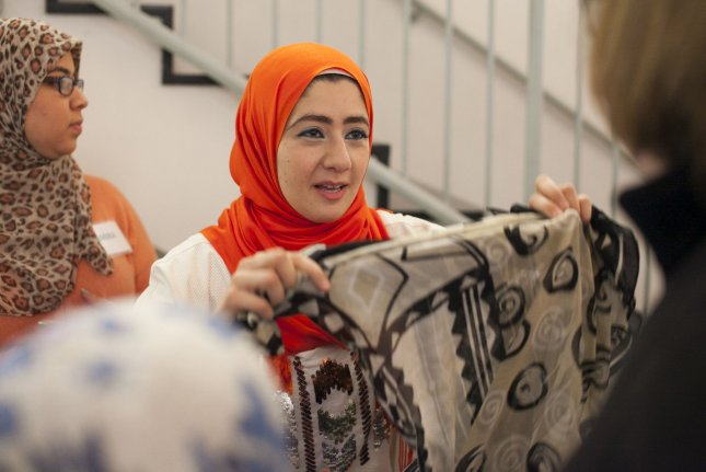 Volunteer Asma Kayal (C) demonstrates how a Hijab is worn during 'Meet-a-Muslim' day at the Worcester Islamic Center in Worcester, Massachusetts. File Photo by Matthew Healey/UPI