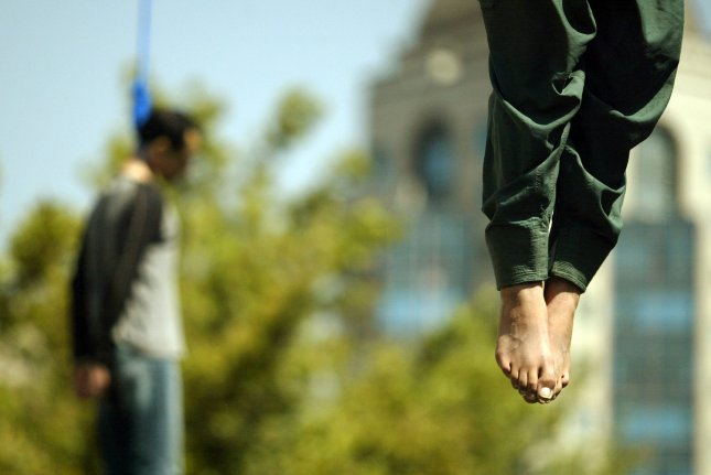 Majid Kavousifar, 28 (L) and Hossein Kavousifar, 24, the convicted murderers of Hassan Moghaddas, a hardline deputy prosecutor and head of the guidance court in Tehran, are publicly hanged in central Tehran, Iran on August 2, 2007. (UPI Photo/Mohammad Kheirkhah)