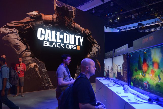 Attendees mill around the Call of Duty Black Ops III video game poster at the Sony PlayStation booth at the Electronic Entertainment Expo, or E3, in Los Angeles on June 18, 2015. New research suggests violent video games may offer stress relief, but may also cause players to perceive the world as hostile. Photo by Jim Ruymen/UPI
