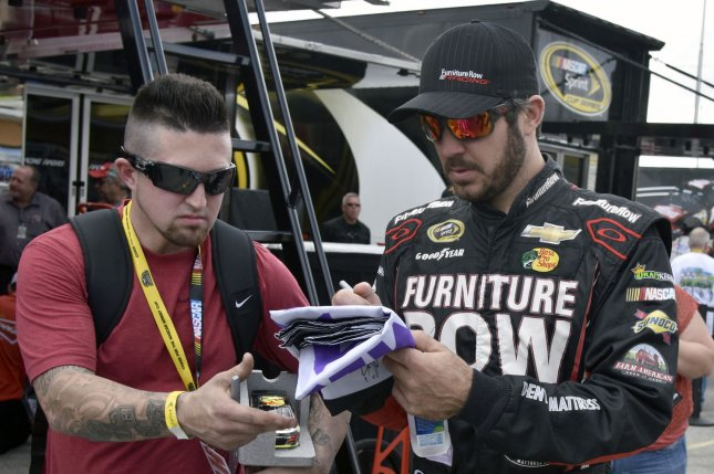 NASCAR Nationwide Series Championship racer Martin Truex Jr. (78) stops to sign autographs. Photo By Gary I Rothstein/UPI