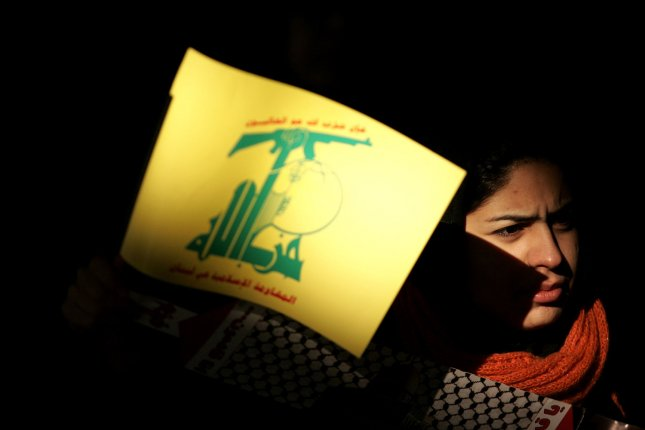A poster displaying Hezbollah's sign is carried during a demonstration in at Tehran University. The assassination of a Sunni cleric who supported Hezbollah has intensified sectarian passions in Lebanon. (UPI Photo/Mohammad Kheirkhah)