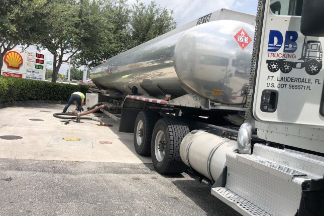 A tanker unloads gasoline into the underground tanks at a station in South Florida. The IEA report Tuesday said less driving and depressed air travel are major factors in the revised outlook. File Photo by Gary I Rothstein/UPI