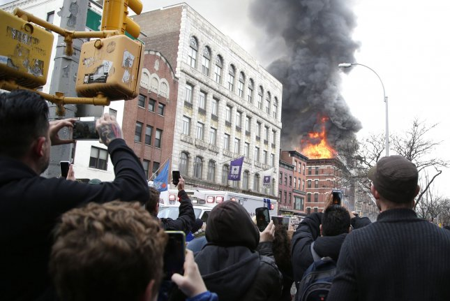 People stop to watch FDNY firefighters put water on a building that is on fire in New York City on March 26, 2015. A powerful explosion in the East Village caused one building to collapse and ignited a large fire that engulfed a neighboring building on Thursday afternoon, leaving at least a dozen people injured, at least three of them critically. Photo by John Angelillo/UPI