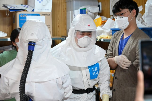 Healthcare workers in Level D protective gear prepare to work with COVID-19 patients at Keimyung University Dongsan Medical Center, a hospital in Daegu, South Korea, on March 24. World Health Organization and South Korean health officials are investigating reports that people who have appeared to recover from COVID-19 later test positive for the disease. Photo by Thomas Maresca/UPI
