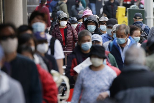 People gather and form a line for food distribution in the Chinatown section of Manhattan during the COVID-19 pandemic in New York City on Tuesday. The world is nearing a milestone 5 million confirmed cases of the virus. Photo by John Angelillo/UPI