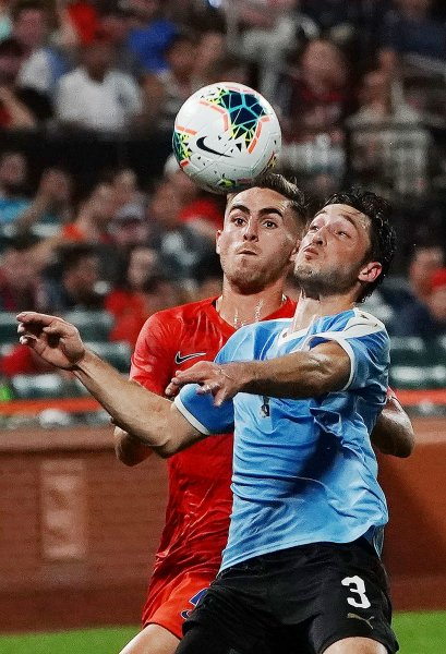Uruguay's Matias Vina and USA's Tyler Boyd keep eyes on the ball in the first half of their international friendly game at Busch Stadium in St. Louis on Tuesday, September 10, 2019. File Photo by Bill Greenblatt/UPI