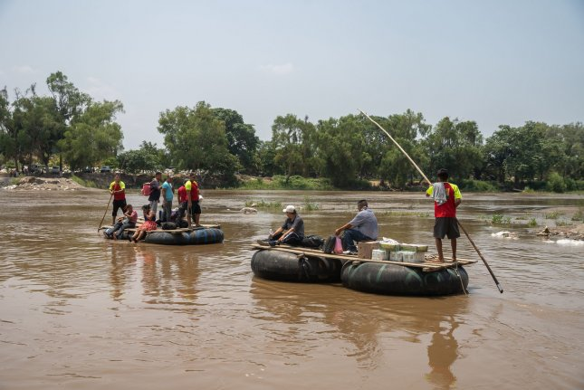 Rafts made out of inflatable tires ferry people and goods across the Suchiate River separating Tecun Uman, Guatemala, and Ciudad Hidalgo, Mexico, on May 9 . File Photo by Ariana Drehsler/UPI