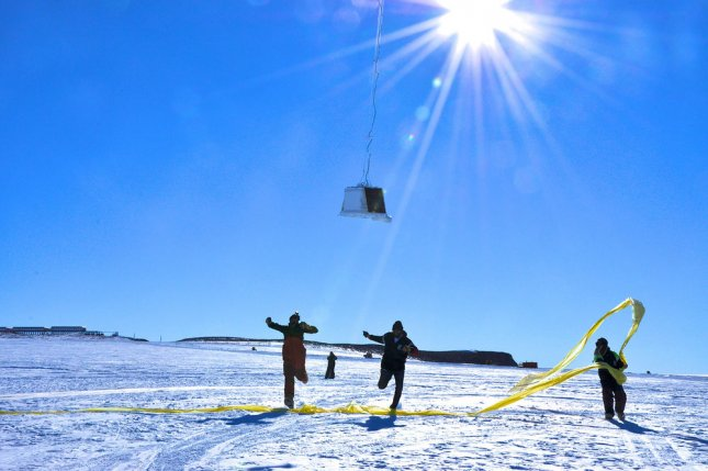 Researchers run under the payload as a balloon first takes flight at the SANAE IV research station in Antarctica. On December 1, 1959, the United States and the Soviet Union signed a treaty banning military activity on Antarctica, reserving the continent for scientific research. File Photo courtesy of NASA