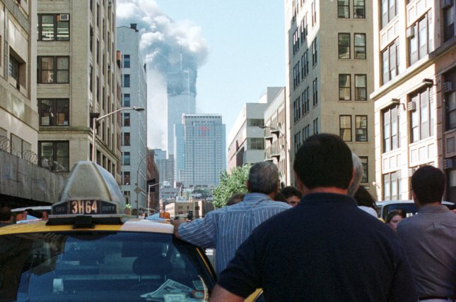 Stunned witnesses watch the World Trade Center burn as they listen to the radio of a stopped taxi cab following the terrorist attacks in New York City on Sept. 11, 2001. Friday, Congress released more than two dozen previously classified pages of a joint congressional inquiry in 2002 that gathered and disseminated intelligence as part of the U.S. investigation into the attacks. File Photo by Monika Graff/UPI