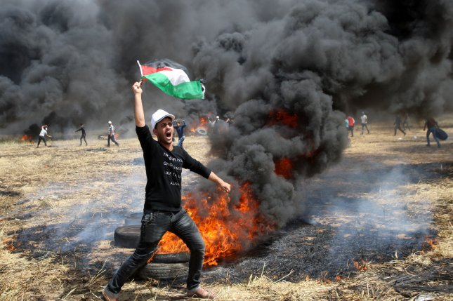 A Palestinian man holds his national flag as others burn tires to protect themselves from shots of Israeli soldiers at the Israel-Gaza border on Friday. A video from a few months ago shows Israeli snipers cheering as a Palestinian man is shot on the border. Photo by Ismael Mohamad/UPI