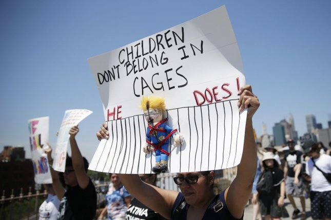 Demonstrators hold signs on the Brooklyn Bridge in New York City on June 30 at the End Family Separation rally and march. A congressional investigation has found nearly 1,500 more migrant children have not been accounted for by federal officials. File Photo by John Angelillo/UPI