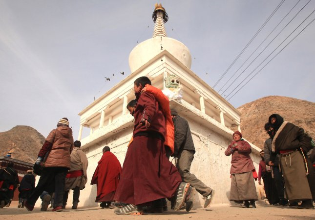 Tibetan nomads, pilgrims and monks walk around a white stupa at the Labrang Monastery, the largest Tibetan monastery outside of Lhasa, prior to the Tibetan Monlam Festival in Xiahe, Gansu Province on the Tibetan plateau, February 2, 2012. Tens of thousands of Tibetans are celebrating the Tibetan New Year by making their way to this town and its Labrang Monastery, whose separation from the Tibetan Autonomous Region provides a measure of protection from Han Chinese attempts to regulate their culture. Photo by Stephen Shaver/UPI