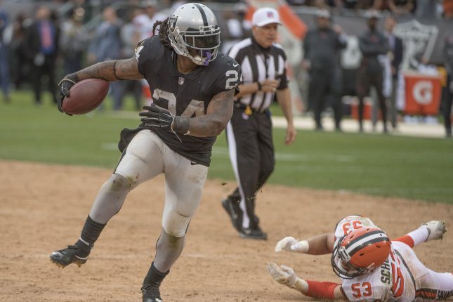 Oakland Raiders running back Marshawn Lynch (24) runs away from Cleveland Browns defender Joe Schobert (53) for 11 yards in overtime on Sunday at the Coliseum in Oakland. Photo by Terry Schmitt/UPI