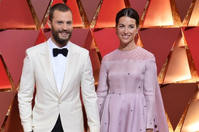 Jamie Dornan (L), pictured with Amelia Warner, recently welcomed a third daughter with the actress and musician. File photo by Jim Ruymen/UPI