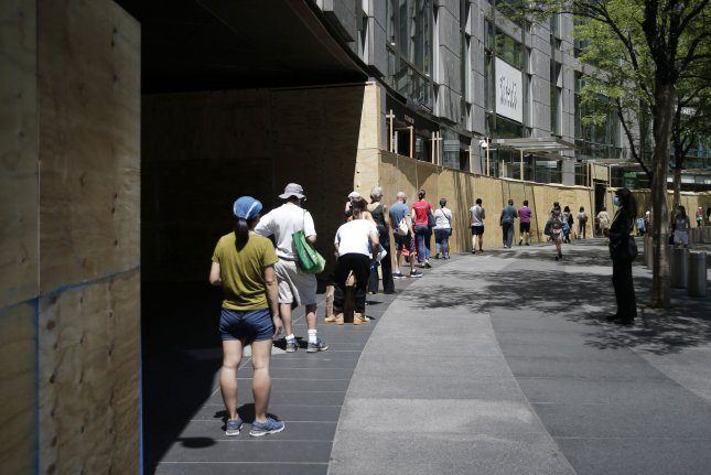 People wait in line near the boarded-up windows at the Shops at Columbus Circle in New York City on Friday. The CDC predicted Friday that up to 140,000 people in the United States could die from the coronavirus by July 4. Photo by John Angelillo/UPI
