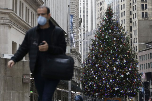 A masked man walks near the Christmas tree last Friday outside at the New York Stock Exchange on Wall Street in New York City. Photo by John Angelillo/UPI