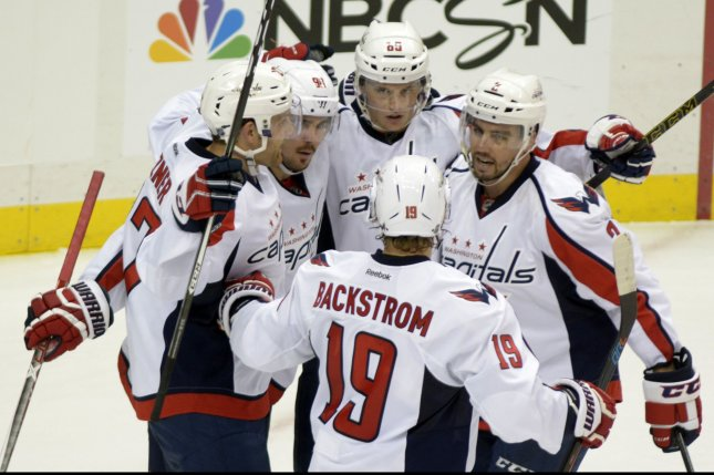 Washington Capitals center Nicklas Backstrom (19) joins the celebration of Washington Capitals left wing Andre Burakovsky (65) goal in the third period of the Pittsburgh Penguins 3-2 overtime shoot-out win of their Home Opener at the PPG Paints Arena in Pittsburgh on October 13, 2016. UPI/Archie Carpenter