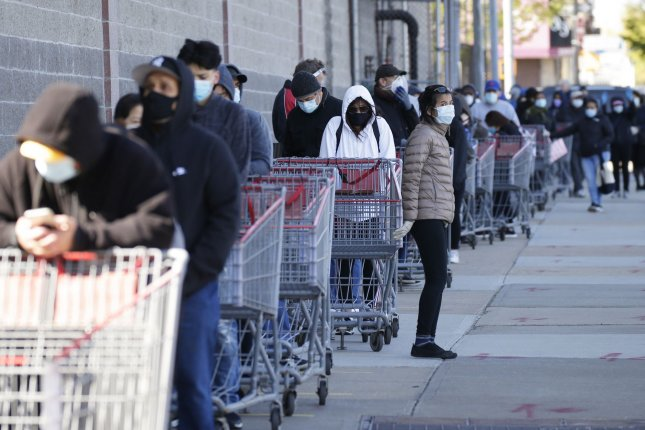 Shoppers wait to enter a Costco store in New York City on Tuesday. Lines at various stores nationwide have been longer since the start of the coronavirus crisis.  Photo by John Angelillo/UPI