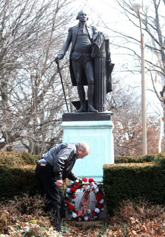 Jack Swanson retrieves a flower wreath following ceremonies for President's Day at the George Washington statue in Lafayette Park in St. Louis, Feb. 20, 2012. UPI/Bill Greenblatt