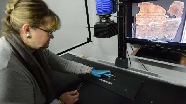 A conservation analyst from the Israel Antiquities Authority photographs a fragment of the 2,000 year old Dead Sea Scrolls at a laboratory in Jerusalem, Israel, December 18, 2012.The Israel Antiquities Authority and Google Israel announced the publishing of the Dead Sea Scrolls Digital Library online at a press conference today. The digital library will eventually hold tens of thousands of fragments of the Dead Sea Scrolls in high resolution photographed with a special camera based on NASA technology. UPI/Debbie Hill.