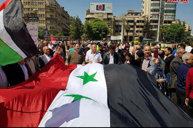Syrians wave the national flag and portraits of President Bashar al-Assad as they gather at Square in Damascus on April 14. Photo by SANA/UPI