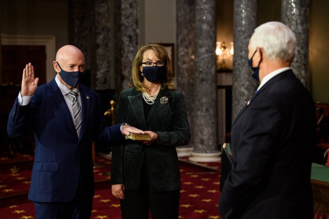 Former astronaut Mark Kelly (L) is sworn in to the U.S. Senate during a reenactment by Vice President Mike Pence (R) as his wife, former Rep. Gabby Giffords, looks on at the U.S. Capitol in Washington, D.C., on Wednesday, Pool Photo by Nicholas Kamm/UPI