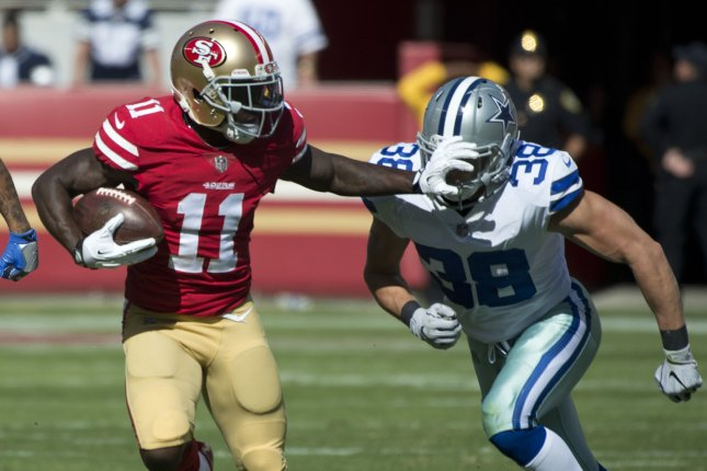 San Francisco 49ers Marquise Goodwin (11) holds off Dallas Cowboys Jeff Heath (38) as he takes a C.J. Beathard pass 48 yards in the first quarter at Levi's Stadium in Santa Clara, California on October 22, 2017. Elliott ran for 147 yards as the Cowboys whopped the winless Niners 40-10. Photo by Terry Schmitt/UPI
