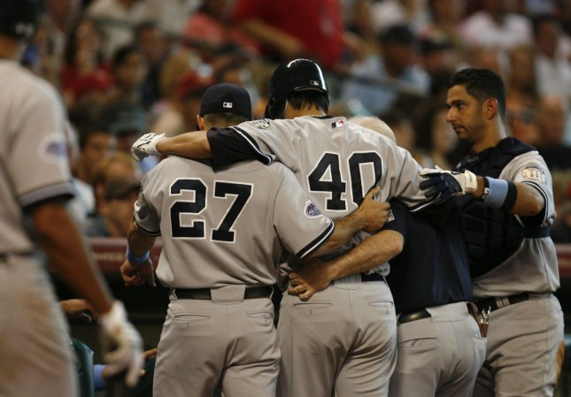 New York Yankees starting pitcher Chien-Ming Wang (40), shown here being helped off the field after hurting his right foot during a game in Houston June 15, will be out for the regular season, possibly returning if the Yankees make into the playoffs. (UPI Photo/Aaron M. Sprecher)
