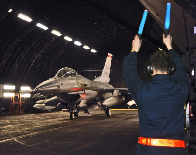 A crew chief from the 52nd Aircraft Maintenance Squadron marshals an F-16 Fighting Falcon out of a hardened aircraft shelter at Spangdahlem Air Base, Germany, in support of Operation Odyssey Dawn, March 20, 2011. Joint Task Force Odyssey Dawn is the U.S. Africa Command task force established to provide operational and tactical command and control of U.S. military forces supporting the international response to the unrest in Libya and enforcement of United Nations Security Council Resolution (UNSCR) 1973. UPI/Benjamin Wilson/US Air Force