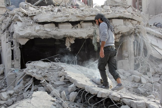 A Syrian man inspected a building struck by a Russian missile Oct. 30. Three Russian journalists were injured Monday, as they visited the front lines of combat near the Turkey-Syria border. Photo by Ameer Alhalbi/UPI