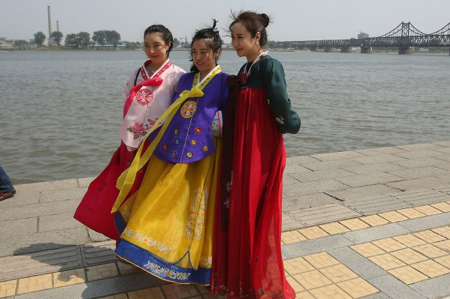 Chinese women dressed in traditional North Korean dress pose for pictures in Dandong, China. The number of Chinese tourists to North Korea on half-day package tours have recently dropped due to waning popularity, according to Yonhap. File Photo by Stephen Shaver