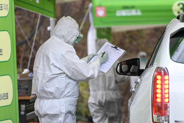Health workers in biohazard suits treat patients at a drive-through coronavirus testing center at Seoul Metropolitan Eunpyeong Hospital on March 4. Photo by Thomas Maresca/UPI