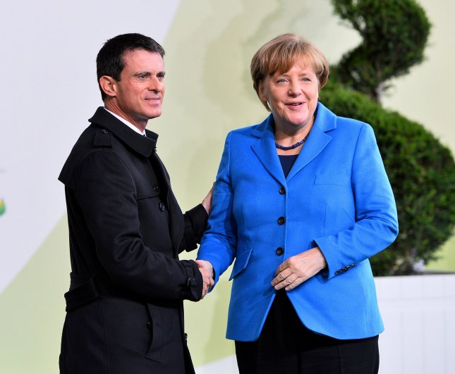 German Chancellor Angela Merkel (R) is greeted by French Prime Minister Manuel Valls at the United Nation's 21st climate change conference at Le Bourget near Paris on November 30. She recently spoke in favor of stronger deportation laws after facing pressure for her open-door immigration policies, intensified by New Year's Eve sexual assaults in Cologne. Photo by David Silpa/UPI
