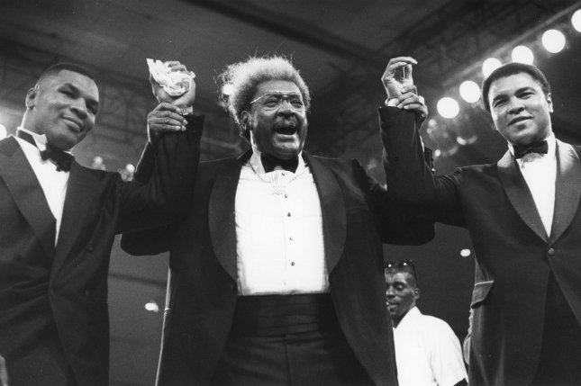 Boxing promoter Don King (C) poses in the ring with former heavyweight champions Mike Tyson (L) and Muhammed Ali on October 29, 1988. Mike Tyson, Will Smith, and Lennox Lewis will be pallbearers for Ali's funeral on Friday. File photo by Paul Richards/UPI